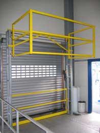Das Bild zeigt eine weitere Bauweise eines Sicherheitsschleusengeländers. Durch schliessen einer vertikalen Gleitschranke an der Bühnenkante, öffnet sich der Schleusenkorb nach oben und ermöglicht die Palettenentnahme.